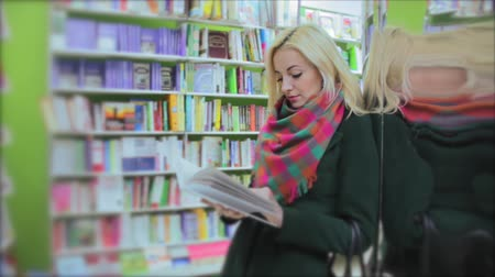 книги : Young woman in a book store Стоковые видеозаписи