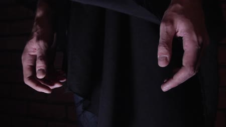 jail bars : Close Up of Prisoner hands in the hood in a dark cave Stock Footage