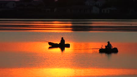 göl : Fishing boats on the lake at  Sunset, village on background Stok Video