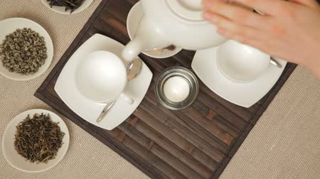 herbal : Woman pours green tea from teapot into a couple of cups, which stands on a table surrounded by various kinds of tea Stock Footage