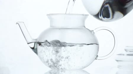 demlik : Woman puts  Green Chinese flower tea in the glass teapot and pours boiling water
