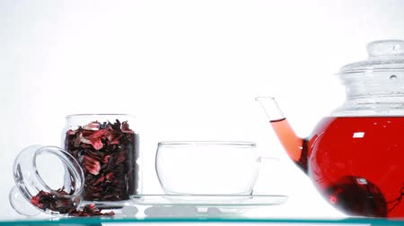 hibiscus tea : Woman pours red Hibiscus tea from glass teapot into glass Stock Footage