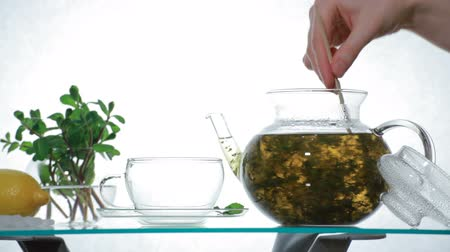 herbal : Time-lapse Woman puts  Green Chinese flower tea in the glass teapot and pours boiling water