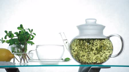 herbal : Time-lapse Woman puts Chinese herbal tea in the glass teapot and pours boiling water Stock Footage