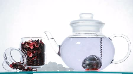 hibiscus tea : Time-lapse Woman puts red Hibiscus tea  in the glass teapot and pours boiling water
