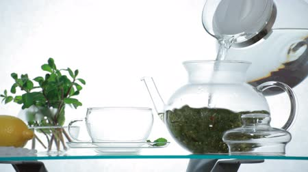 herbal : Woman puts Chinese herbal tea in the glass teapot and pours boiling water Stock Footage