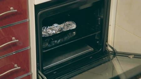 forno : Young woman with yellow kitchen freeze opening  kitchen oven and pulling out of it on baking sheet wrapped in foil piece of pork, puting it on the table and carefully so as not to burn herself, expanding the foil. Do you feel a scent coming from this yumm