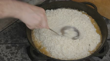 cop : Spreading rice on the surface of cauldron with slotted spoon, then filling with water from the kettle to the brim, trying to cover full pilaf. EDIT 2 CAMS