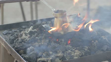 bronz : Flames rising above the hot coals, covering the pot in which coffee is brewed as in the ancient times, close-up Stok Video