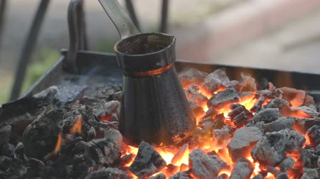 cooking pots : Already charred pot, in which coffee is brewing, standing at the progressively fading embers.