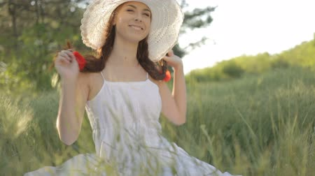 csak a fiatal nők : Young woman in white sundress and hat with red poppies in hair resting on the nature in forest sitting on the grass, smiling, flirting.