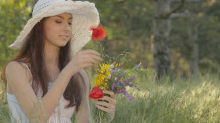 только один человек : CLIP EDIT Young woman in white sundress and hat forming bouquet of wild flowers, resting on nature in forest, sitting among grass, smiling, flirting, touching and smelling flowers. Стоковые видеозаписи