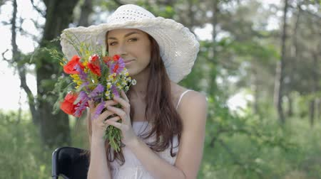 csak a fiatal nők : Young woman in white sundress and hat with bouquet of wild flowers has a rest on the nature in forest sitting on a chair smiling, flirting, touching and smelling flowers Stock mozgókép