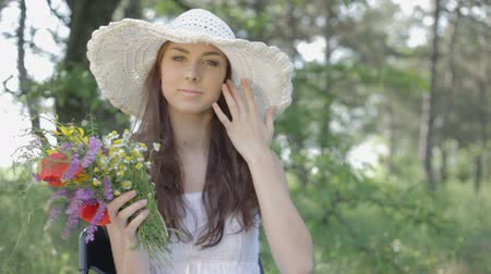 только один человек :  CLIP EDIT Young woman in a white sundress and a hat with a bunch of wild flowers has a rest on the nature in forest sitting on a chair touching hair smelling flowers