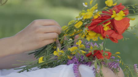 только один человек : Young woman in a white sundress sitting with a bunch of wild flowers