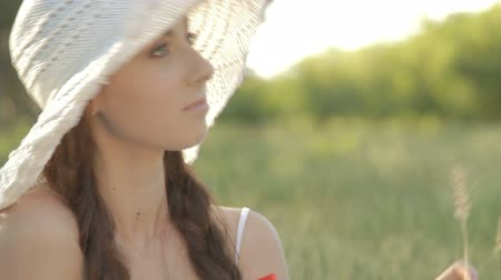 despreocupado : Young woman in a white sundress and a hat with plaits on her head  sitting on a grass, looking away