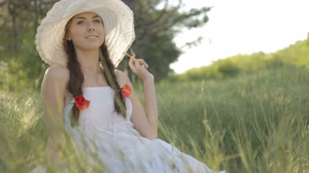 rests : Young woman in a white sundress and a hat with plaits on her head  sitting on a grass