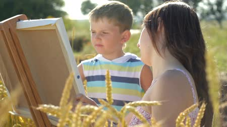 aktywność : Young woman with little boy drawing together with crayons on white canvas paper in front of wheat field, communicating, enjoying free time, smiling.