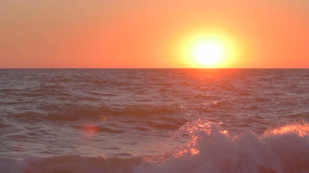 shoreline : Beautiful sunset over the sea, waves hitting the shore, white drops of sea foam rise above the water surface. Stock Footage