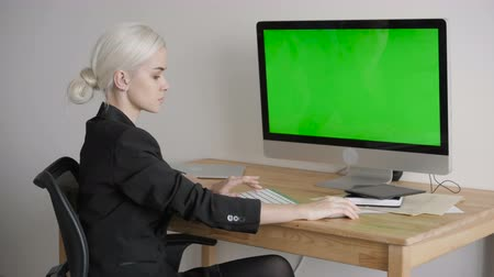 titkár : Young Woman Using Computer With Green Screen Display Stock mozgókép