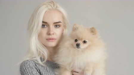 animais e animais de estimação : Cinemagraph Beautiful Blonde Woman With Her Spitz Isolated On Grey