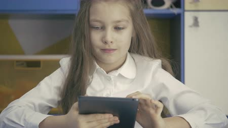 latino americana : Cute little Girl Studying at the Library Doing Homework with Tablet PC