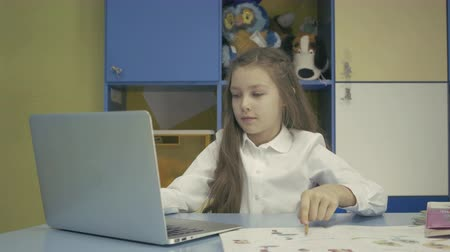 gal : Young girl Using a Laptop and Doing Homework in School