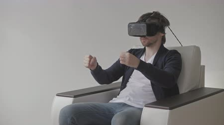 simülasyon : Man Wearing Virtual Reality Glasses Watching Movies or Playing Video Games.  VR Headset technology concept. Stok Video