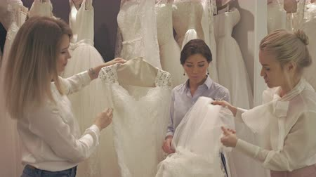 pomocník : Smiling Pretty Group of Brides Chooses White Dress at Shop of Wedding Fashion