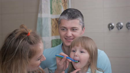 herança : Mother and father teaching little daughter clean teeth