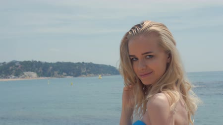 outside : Portrait of attractive woman standing at beach. Happy smiling girl looking at camera at seaside. Young blonde woman relaxing at beach. Stock Footage