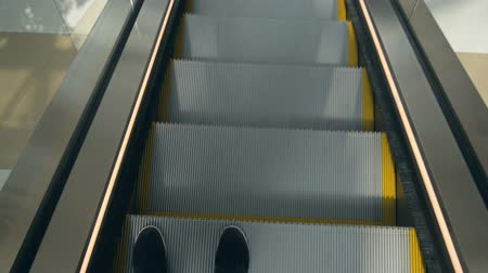 escalope : The photo with legs on escalator top view Stock Footage