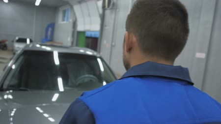 szerelő : Professional car mechanic working in modern auto repair service and checking engine