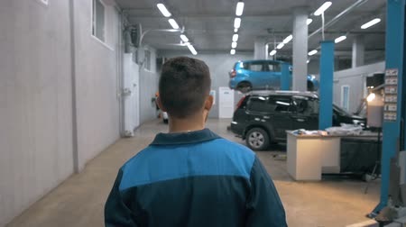 část těla : Professional car mechanic working in modern auto repair service and walking around