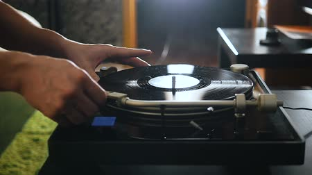 arranhão : Turntable playing music with hand with backlight. Oldschool hipster concept.