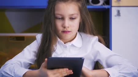 гимназия : SchoolGirl Studying at the Library Doing after lessons Homework with tablet PC. Elementary school. Child reading. Стоковые видеозаписи