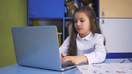 домашнее задание : SchoolGirl Studying at the Library Doing after lessons Homework with laptop PC. Elementary school with devices. Child reading. Стоковые видеозаписи