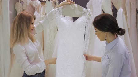 asistan : Female shop consultant helps bride chooses dress at shop of wedding fashion. Focus on girl.