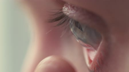 soczewki kontaktowe : Young handsome man putting contact lens in her eye close up.