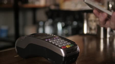 плата : Customer paying with NFC technology by mobile phone on terminal in modern cafe Стоковые видеозаписи