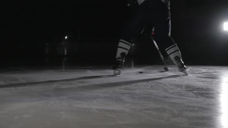 hockey rink : Hockey player make ice sparkles on high speed braking. Motion blur. Legs view only