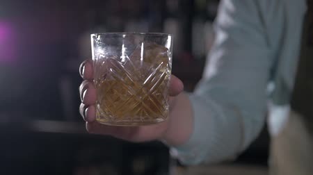 detém : Hand holding a glass of whiskey on the rock in bar. Man shake alcohol in bar.