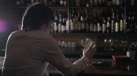 держит : Hand holding a glass of whiskey on the rock in bar. Man shake alcohol in bar.