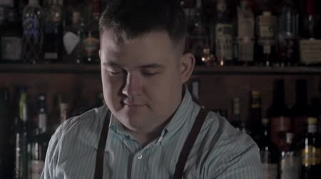 double happiness : Smiling barman serving cocktail in pub. Handsome bartender give whiskey with zest. Stock Footage