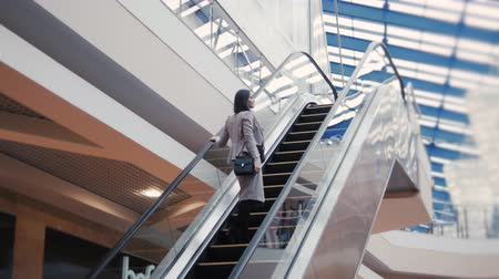 mozgólépcső : Full length of confident businesswoman standing on escalator with laggage in airport. Business woman with suitcase in mall.