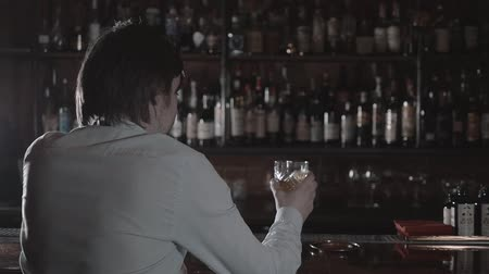 zengin : The night is young. Closeup shot of a handsome man looking away thoughtfully drinking whiskey at the bar Stok Video