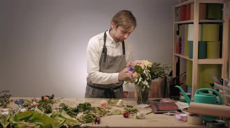 floral composition : Small business. Male florists making rose bouquet in flower shop. Man owner and assistant in floral design studio, making decorations and arrangement. Flowers delivery, creating order Stock Footage
