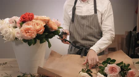 floral composition : Male florist hands closeup, cuts rose for bouquet in flower shop. Man assistant or owner in floral design studio, making decorations and arrangements. Flowers delivery, creating order. Small business.