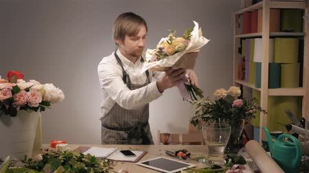 floral composition : Handsome bearded florist with tablet computer at workplace taking order by phone in modern flower shop Stock Footage