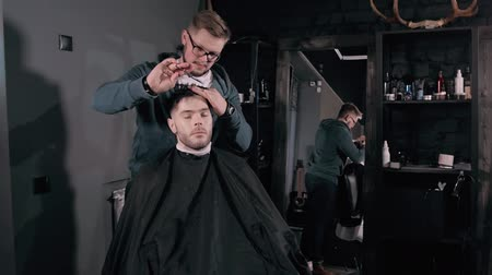 kadeřník : Making haircut look perfect. Young bearded man getting haircut by hairdresser while sitting in chair at barbershop, hairdresser styling.